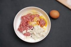Minced mięso w pucharze z pikantność i jajkiem na Ciemnym tle Odgórny widok, czarny tło fotografia royalty free