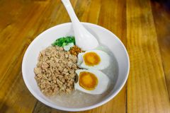 Minced pork congee with egg, fresh ginger. And coriander on white cup and spoon over the wood table. Second view royalty free stock photos