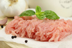 Minced turkey meat. On wooden cutting board with garlic, fresh basil and black pepper Royalty Free Stock Images