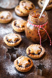 Mincemeat pies. Traditional festive Christmas mince pies with a jar of homemade mincemeat and an empty tag Stock Photos