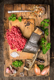 Mincemeat of vintage meat grinder on old wooden table with herbs and spices in spoon. Top view Stock Images
