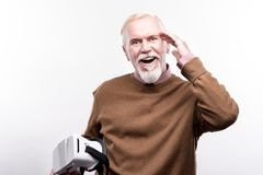Senior man being pleasantly surprised by VR experience. Mind-blowing technologies. Upbeat elderly man touching his head, being pleasantly surprised, having used royalty free stock photography