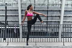 Mind and body in harmony. Full length of modern young woman in sports clothing stretching while warming up outdoors stock photos