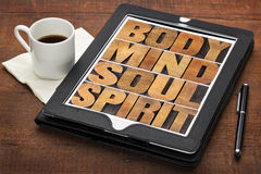Mind, body, soul and spirit. Wellness concept - a collage of words in letterpress wood type on a digital tablet with cup of coffee Royalty Free Stock Photography