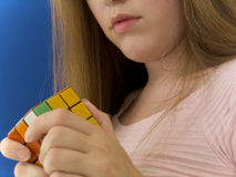 Mind games. Woman concentrated on putting together a magic cube Royalty Free Stock Images