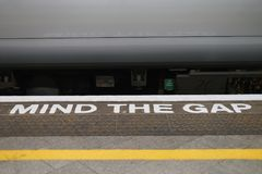 Mind the gap alert. Train station in England. Stock Photos