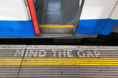 Mind the gap sign with open train door Royalty Free Stock Photos