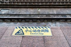 Mind the gap sign painted on train station`s platform edge. Translation from chinese on sign text caution gap Royalty Free Stock Photography