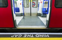Mind the gap sign with speeding train in London underground stock images