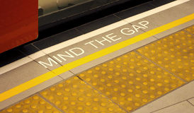 Mind the gap sign on the subway train platform. Stock Images