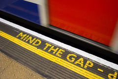 Mind the Gap. Sign with a train moving by it at speed Royalty Free Stock Image