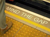 Mind the gap text sign on floor. Royalty Free Stock Photo