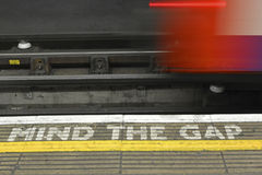 Mind the Gap. Warning and blurred train on electrified rails Stock Photo