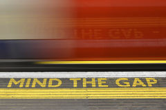Mind the Gap. Warning and blurred underground train with reflection Royalty Free Stock Image