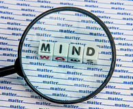 "Mind over matter. Text ""mind"" in uppercase letters inscribed on small white cubes viewed through a hand magnifier against a background of ""matter"" repeated Royalty Free Stock Images"