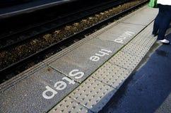 Mind the step sign on railway platform floor Royalty Free Stock Photo