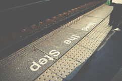Mind the step sign on railway platform floor. Royalty Free Stock Photography