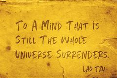 Mind that is still Lao Tzu. To a mind that is still the whole universe surrenders - ancient Chinese philosopher Lao Tzu quote printed on grunge yellow paper royalty free stock image