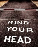 Mind your head. Warning on a street Stock Image