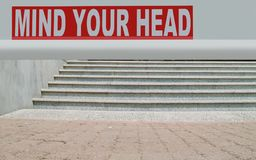 Mind your head. The text of `Mind your head` is written on the white precaution board above the steps. the lover part of picture can be used for your text Stock Photo