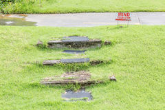 """""""Mind your step"""" warning sign near natural wooden steps on g Stock Image"""