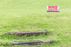 Mind your step warning sign to alert of natural wooden steps on Royalty Free Stock Images