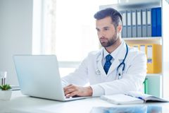 Minded successful doctor sitting at his office and using laptop. For his work Royalty Free Stock Photos