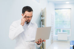 Minded successful doctor standing at his office and using laptop for his work Royalty Free Stock Images