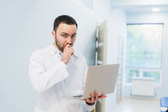 Minded successful doctor standing at his office and using laptop for his work Royalty Free Stock Image