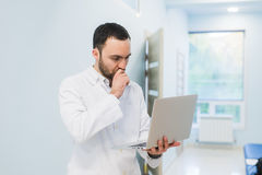 Minded successful doctor standing at his office and using laptop for his work Stock Image