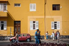 Streets of Mindelo, people against a yellow wall Stock Image
