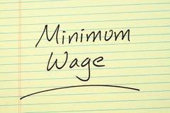Mindestlohn auf einem gelben Kanzleibogenblock Stockbilder
