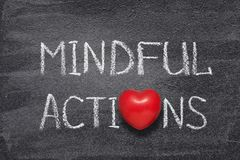 Mindful actions heart. Mindful actions phrase handwritten on chalkboard with red heart symbol instead of O Royalty Free Stock Photography