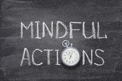 Mindful actions watch. Mindful actions phrase handwritten on chalkboard with vintage precise stopwatch used instead of O Royalty Free Stock Image