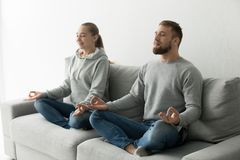 Mindful couple meditating together practicing yoga at home on so. Mindful couple meditating together practicing yoga sitting in lotus pose on sofa at home, calm Stock Photo
