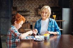 Mindful elderly woman painting with little grandson Royalty Free Stock Image