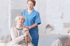 Mindful female caregiver standing next to her senior patient. Always here to help. Selective focus on a charming granny looking into the camera while sitting Stock Photography