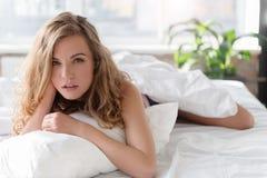 Mindful glancing lady on bedding Stock Image