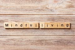 Mindful living word written on wood block. mindful living text on table, concept.  Stock Photography