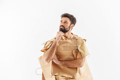 Mindful male person hardly thinking. How can we save environment. Thoughtful man dressed in paper bags is looking up with expectation. Isolated Royalty Free Stock Photography