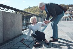 Mindful man helping elderly female stranger to stand up stock photo