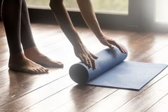 Mindful meditation or fitness session at home concept. Equipment for sport training session concept. Girl wearing grey sporty pants rolling fitness mat before or stock photos