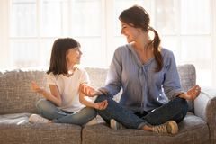 Mindful mom teaching yoga happy child daughter sitting on couch royalty free stock photography