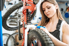 Mindful worker repairing bicycle in the garage Royalty Free Stock Photography