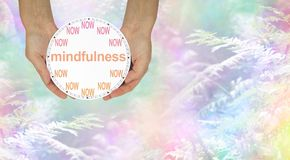 Mindfulness - do it NOW. Female hands holding a NOW clock with MINDFULNESS written across the middle against an ethereal rainbow coloured fern background Stock Image