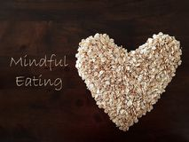 Mindfulness Eating concept using oat formed into a heart shape. Mindful eating concept using oat formed into a heart shape with wood grain table as background royalty free stock photography