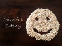 Mindfulness Eating concept using oat formed into a smiley face. Mindful eating concept using oat formed into a smiley face with wood grain table as background stock images