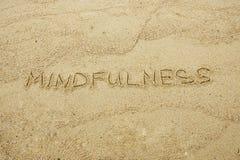 Mindfulness escrito na areia imagem de stock royalty free