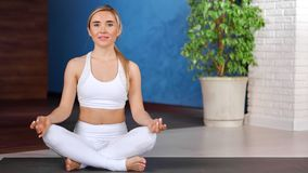 Mindfulness happy fitness woman practicing yoga having positive emotion at modern gym sport studio. Smiling young girl relaxing enjoying meditation sitting in stock video footage