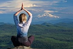 Mindfulness and inner peace. Yoga retreat. Woman meditating by the view of volcano Mount Hood in Oregon. The Dalles.  Portland. Or. United States of America Stock Image